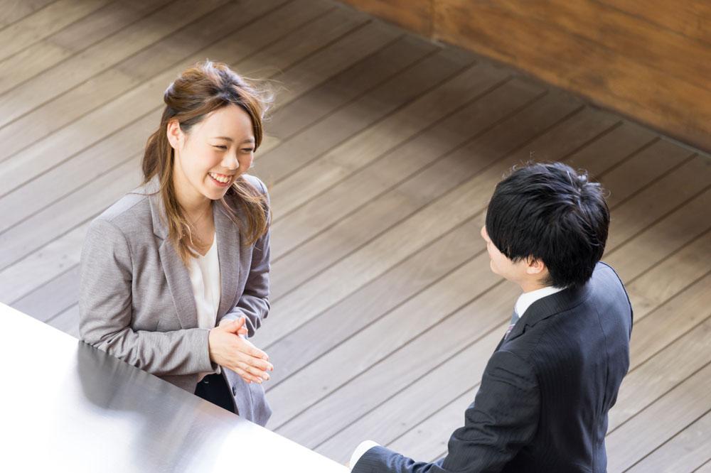 笑顔に加えて正しい言葉づかいで男性と話をする女性