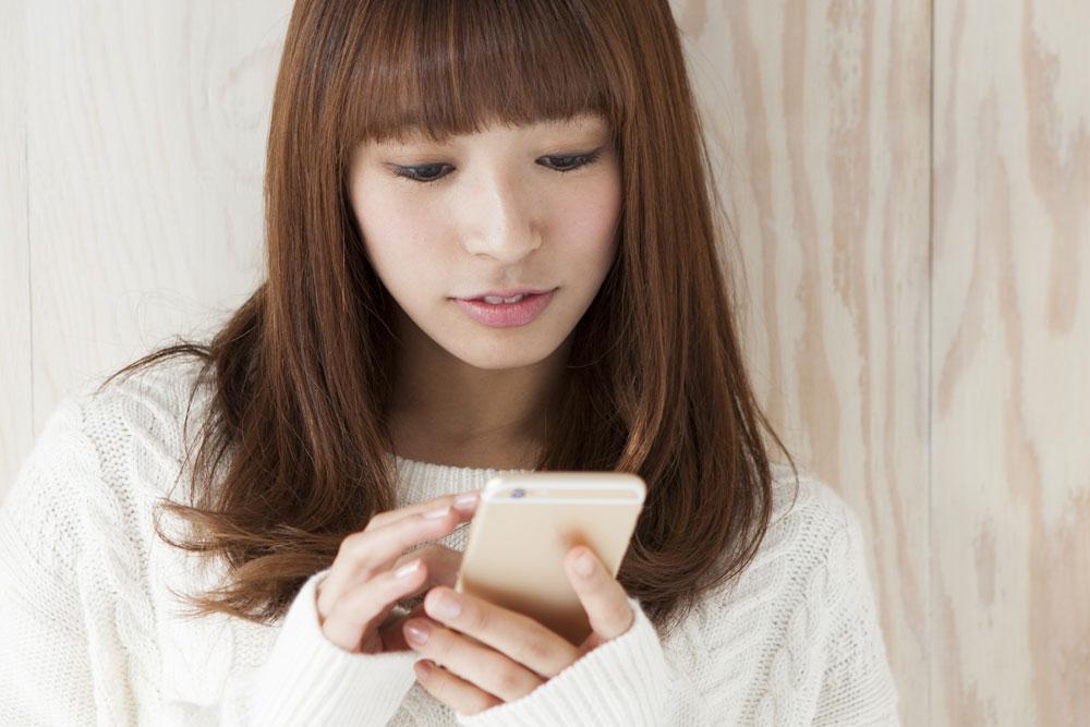 ダブルバインドに使うために、友人に気になる人の情報を教えてもらっている女性